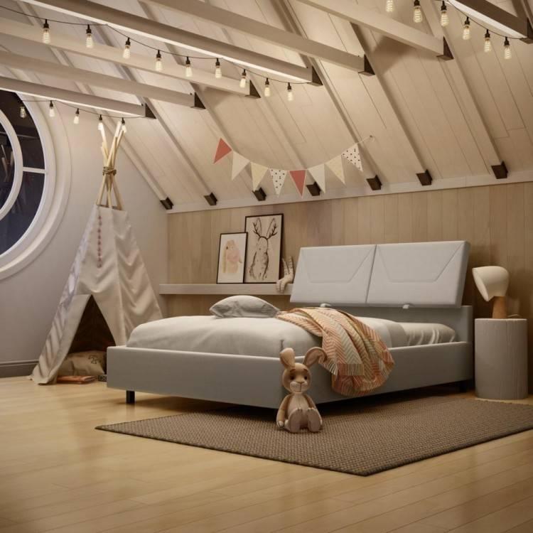 Pouf et plante à côté de lit gris avec coussins roses à l'intérieur de la chambre à coucher avec affiche