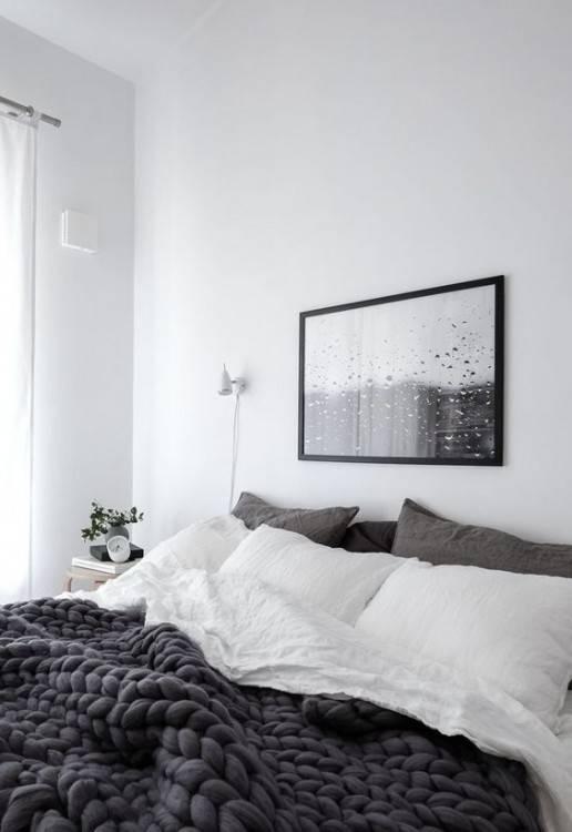 Style Scandi, minimaliste, dépouillé de l'intérieur chambre à coucher avec des meubles de chambre à coucher en bois, murs peints en blanc, des draps blancs,