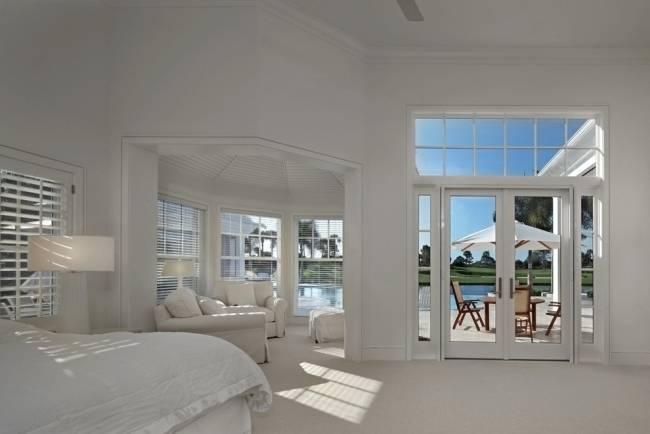 Coin chambre de luxe avec une fenêtre du grenier, les murs en bois et blancs, un plancher de béton, un lit double et un arbre en pot