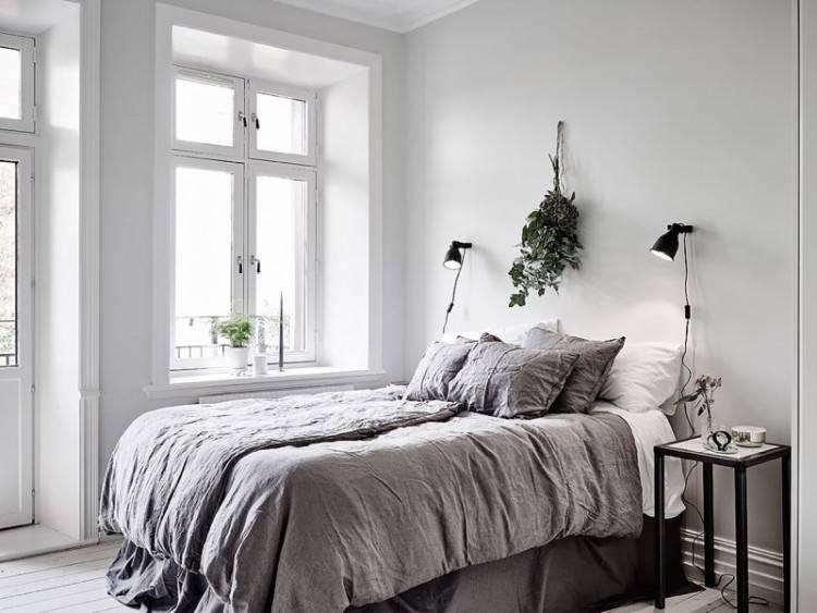 Intérieur chambre à coucher de style scandinave avec murs blancs, un plancher de béton avec un tapis, escaliers et un lit double blanc avec une