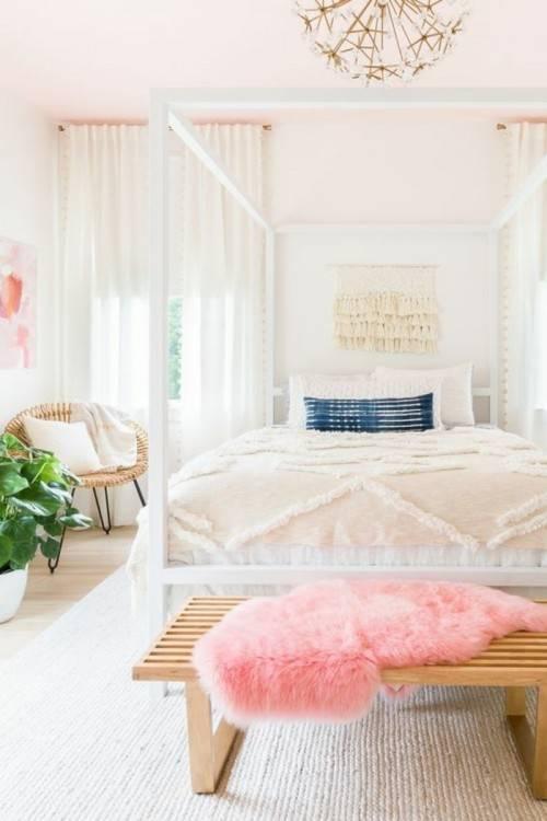 Photo réelle d'une chambre à coucher féminin intérieur avec les feuilles roses sur un lit, debout près de la fenêtre et l'armoire de chevet en bois avec des