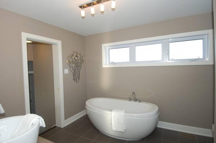 Salle de bains moderne et lumineuse, ensoleillée avec intérieur blanc à montage mural et double lavabo et miroir baignoire sur pieds en face d'une grande