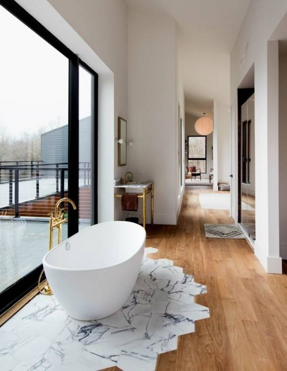 Grande salle de bains moderne avec bidet et lavabo, bain à remous en forme  de bateau sur un parquet en marbre donnant sur un paysage d'hiver brumeux à