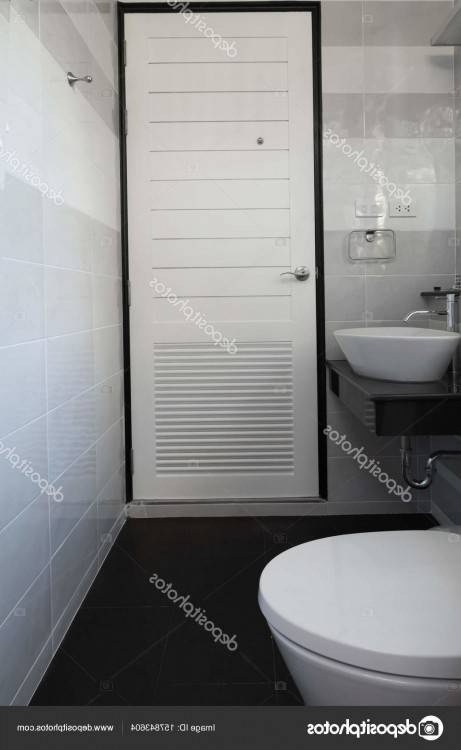 Carrelage noir intérieur de salle de bains moderne avec armoires en bois, une baignoire blanche et un évier
