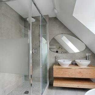Coin salle de bains moderne avec des murs en bois foncés, sol gris, baignoire blanche et double vasque