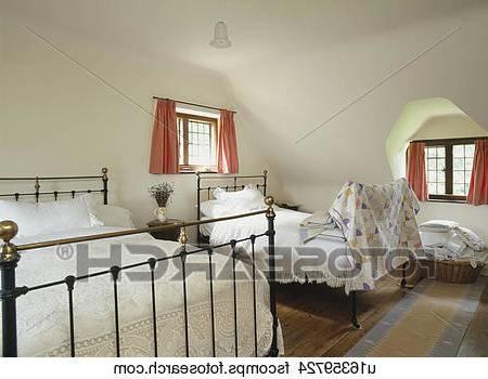 Une chambre à coucher avec deux lits jumeaux, un bureau et une chaise,  l'art de mur, et une fenêtre avec des stores en bois à lattes