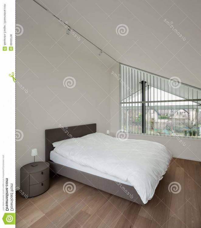Intérieur chambre à coucher moderne avec un élégant décor gris, élégant,  armoires art sur les murs et un parquet en bois en vue d'une cheminée à  foyer