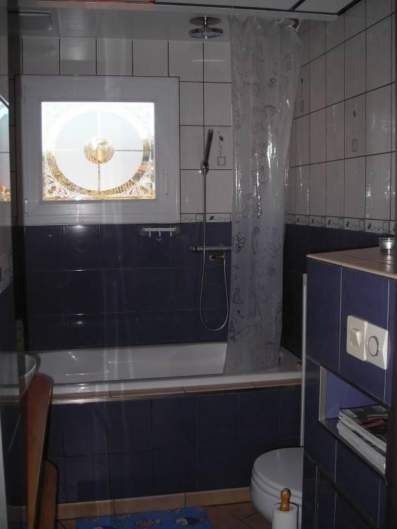 Détail d'une salle de bains moderne avec baignoire encastrée tile surround, fenêtres avec des rideaux, et des cactus en pot