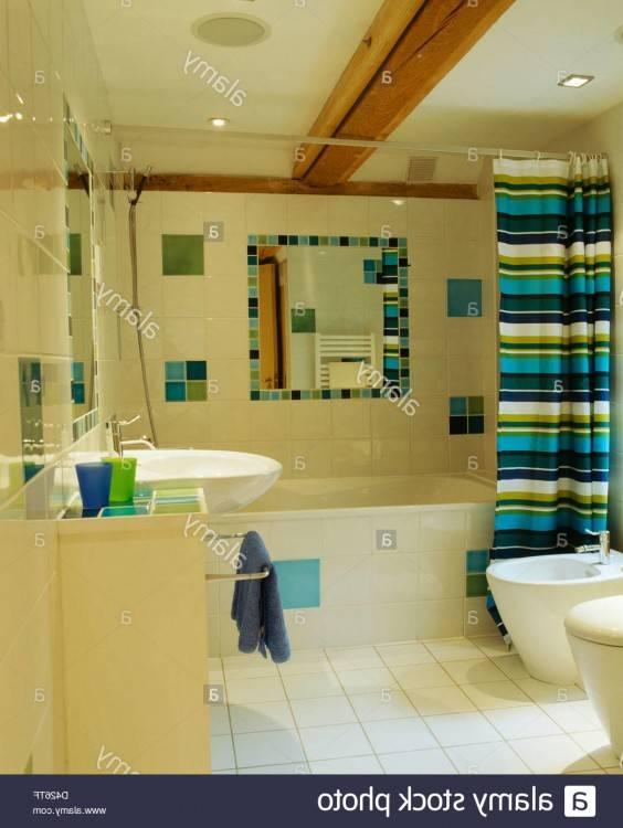 Rideau de douche à rayures de couleurs vives sur la baignoire dans une salle  de bains moderne avec sol carrelé miroir et sol carrelé de couleur crème à