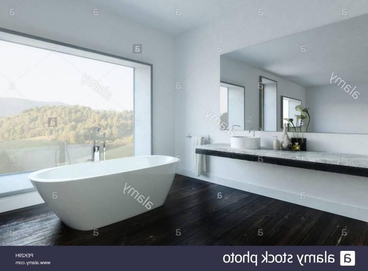 Intérieur de salle de bains moderne avec un sol en marbre, une fenêtre panoramique avec une vue sur la montagne et d'une baignoire blanche